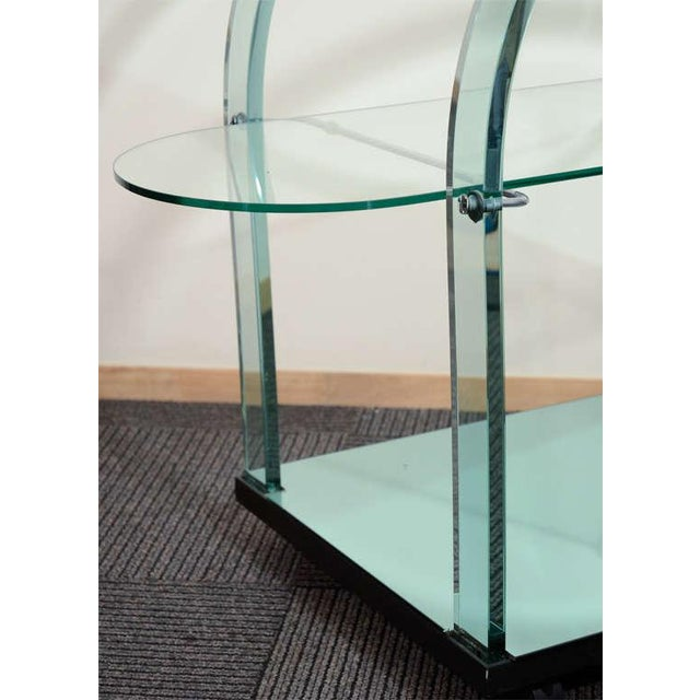 A Modernist French bar cart with arching glass frames supporting an oval glass shelf. The bottom shelf is aqua tinted mirror.