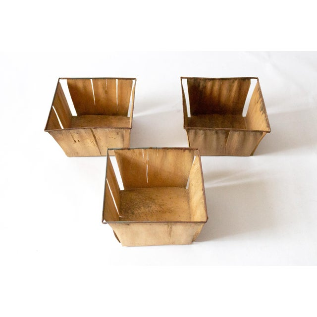 A trio of vintage berry baskets made of thin wood slat sheets and metal. Perfect for corralling cloves of garlic in the...