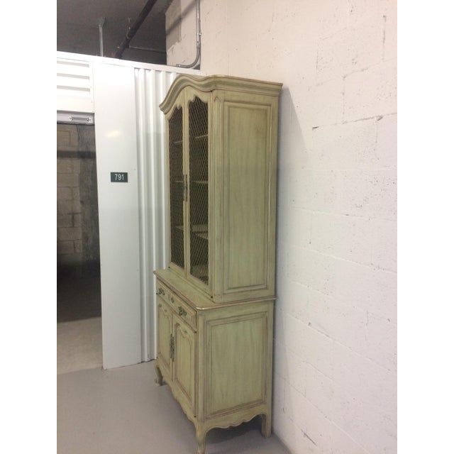 French provincial style 3 drawer step-back cupboard. Drawers below with open mesh doors above with illuminated shelves....