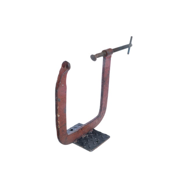 A large industrial C-shape clamp welded to a steel base. A rustic decor piece to add to your home!