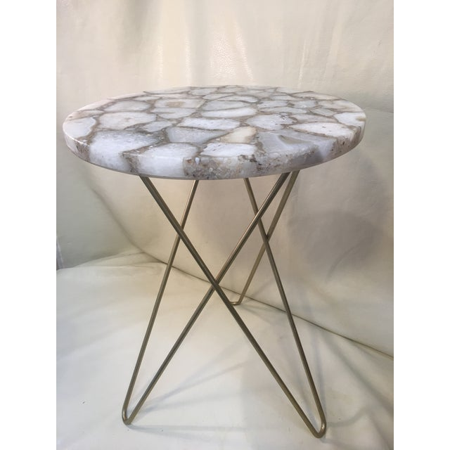 Three steel hairpin legs support this exquisite agate table top in neutral white, brown and gray tones. The legs are gold...