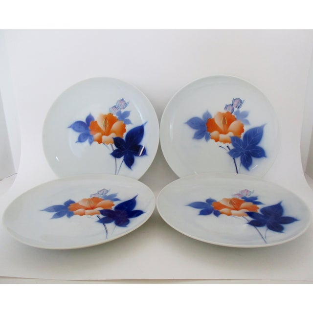 Vintage porcelain salad plates from Japan, finished in white glaze with orange hibiscus flowers with red filaments and...