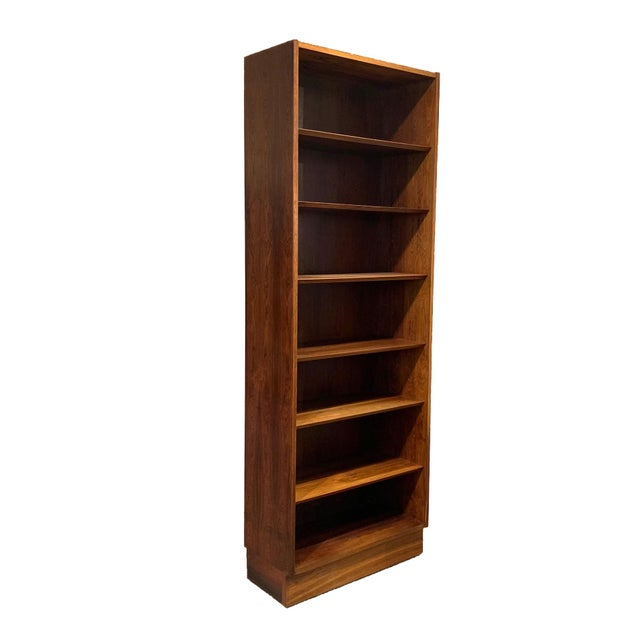 Tall and slender bookcase in Brazillian rosewood. Perfect for a narrow wall space or corner. Six adjustable bevelled edge...