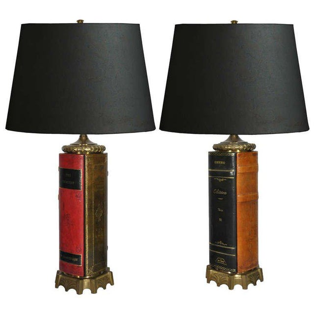 Remarkable quality pair of vintage brass and tooled leather bound book form table lamps. Each lamp features decorative...