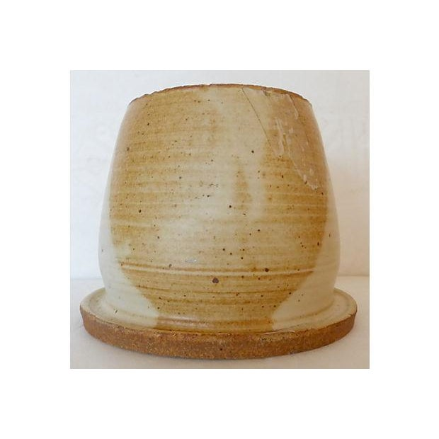 This is a handmade glazed pottery cup or small vase. One very small chip on the rim.