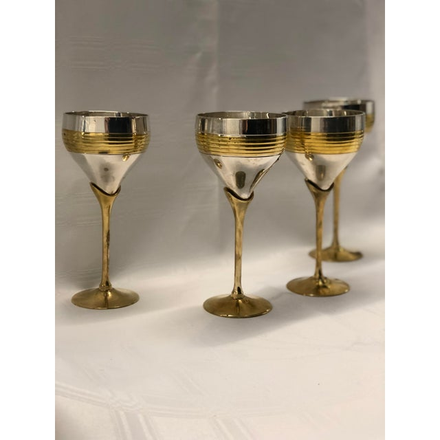 Dynamic vintage set of four wine goblets of heavy brass and chrome with a streamlined Art Deco style form.