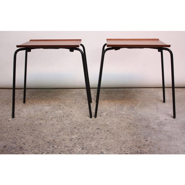 These side or stacking tables are comprised of teak tops with a 'lip' on either side atop enameled metal bases. The...