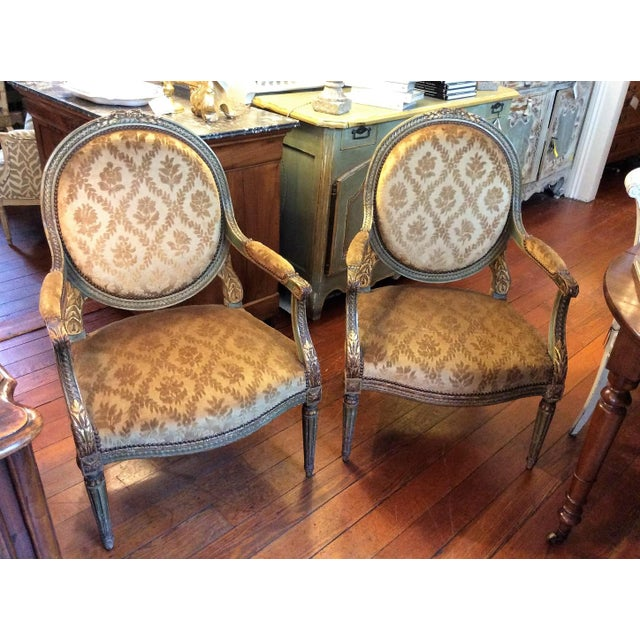 Pair of 19th Century French gilt wood armchairs. Inside carving painted in green. Medallion back with acanthus motif on...