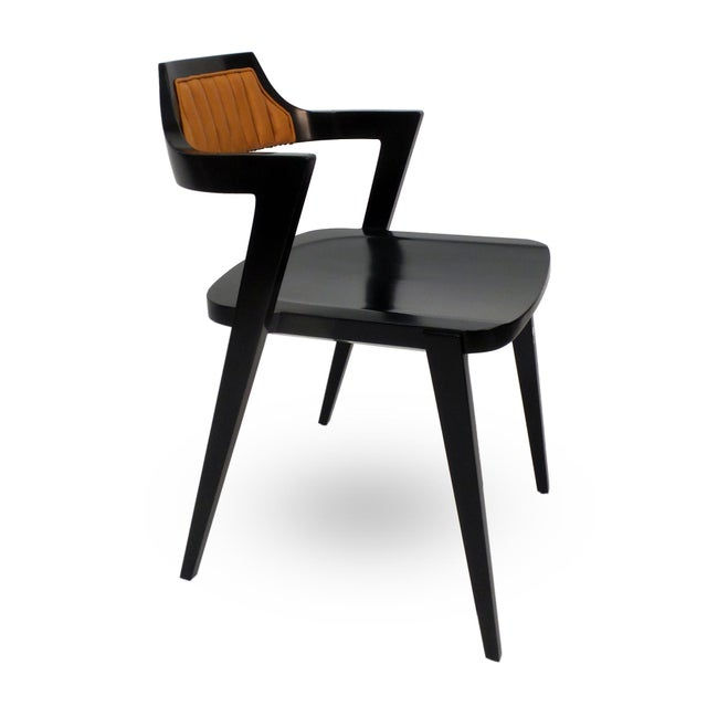 A stackable modern design armchair by Victoria & Son, with forward thrusting arms supporting a cantilevered back having...