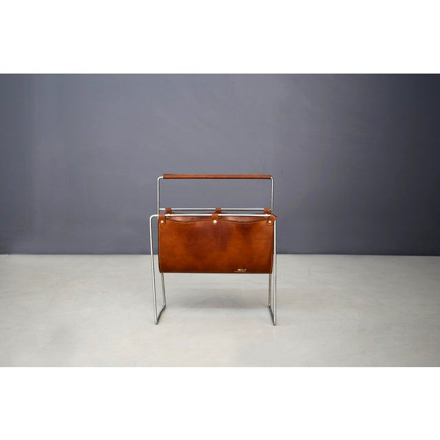 Elegant period magazine rack by Carl Auböck II, Vienna, circa 1950. Its cladding and handle are made of brown leather with...