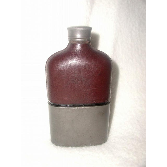 19th century English brown leather flask has nickel lower half with matching screw on cap and cork liner.The glass...