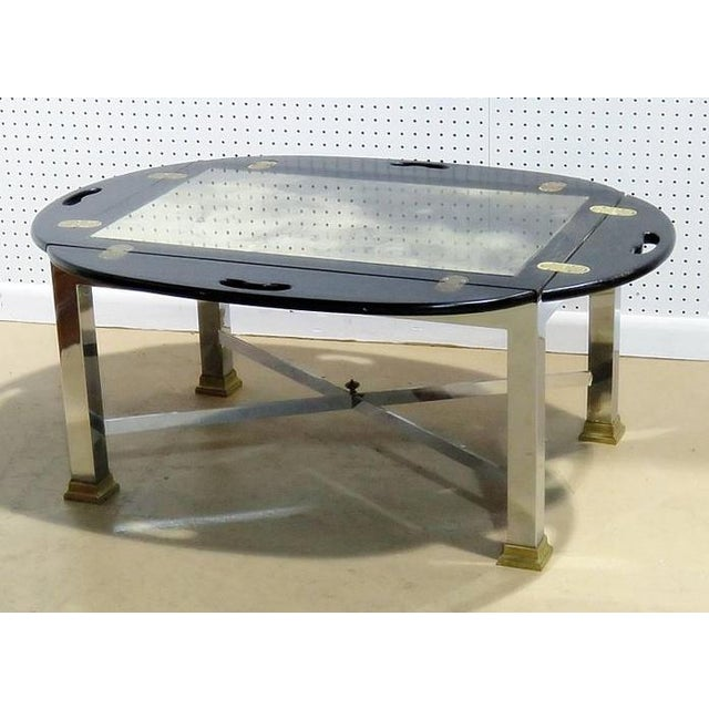 Hollywood Regency style butler's table. Ebonized wood top on a chrome base with brass accents.