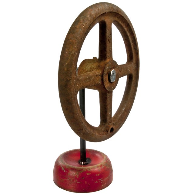 Vintage industrial iron valve handle mounted on a reclaimed iron stand for display. Red base is made from a recycled...