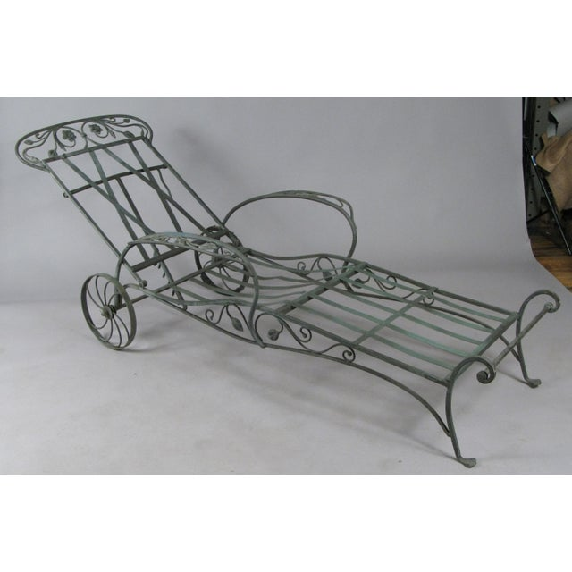 A very well made pair of wrought iron adjustable chaise lounges, made by Salterini, circa 1950, in their blooming rose...