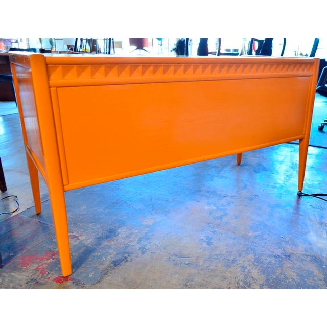 Orange lacquer-painted Broyhill desk with tapered legs, original pulls and a detailed geometric front border. Color is...