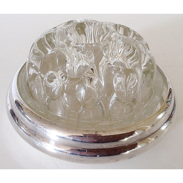 This flower frog, made by the Maison Christofle company in France, has a silver base with a glass insert that has one...