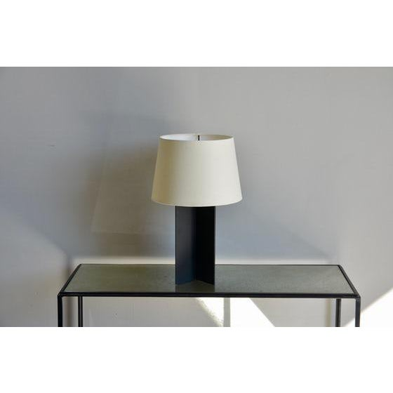 The 'Croisillon' matte black steel table lamp by Design Frères. In the style of Jean-Michel Frank. Custom cream European...