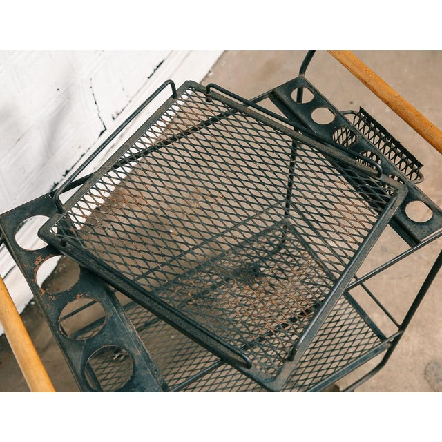 Black metal modernist bar cart. Two diamond mesh tiers and wood dowel handles. The top tier is a separate piece that can...