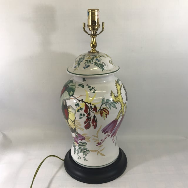 Vintage floral painted ceramic ginger jar shaped table lamp with black painted wood base and brass fittings.