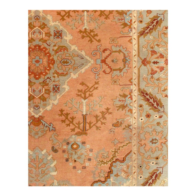 A salmon vision with swaths of yellow and cream, this antique Oushak rug features a botanical theme stitched in pink and...