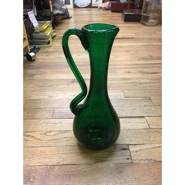 A jewel from The Netherlands! Vivid emerald green elongated art glass pitcher from Royal Leerdam, with fine, irregular...