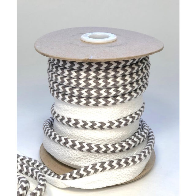 "One 10.9 yard spool of 1/4"" braided cord with 1/2"" flange, total height=3/4"" Cord colors are white and mid-tone gray. This..."