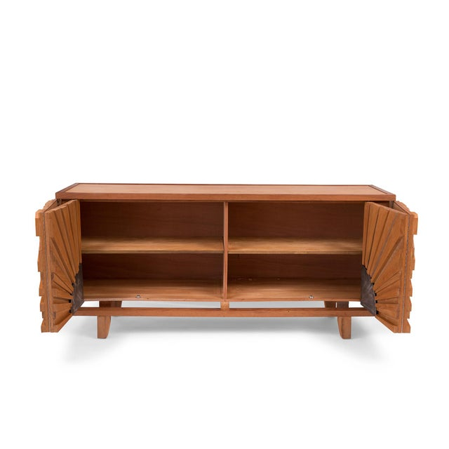 This striking solid teak sideboard by Rafa Mapache is emblazoned with a memorable sunburst pattern carved across its front...