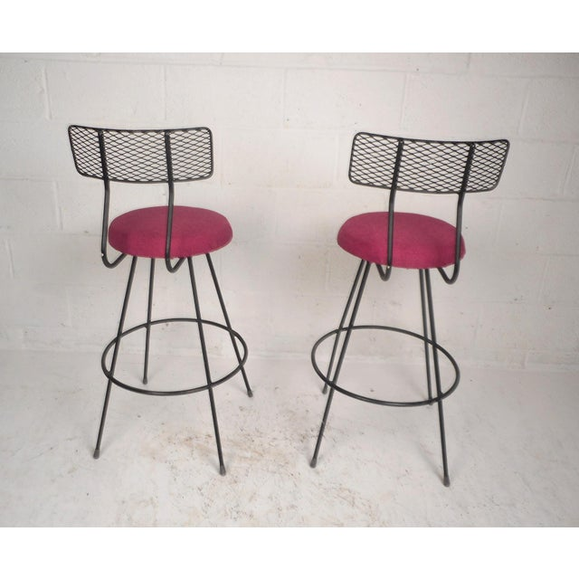 Stunning pair of vintage modern bar stools with grated metal back rests and iron rod bases. Wonderful design with a...