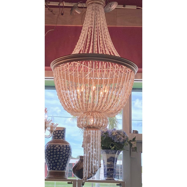 Large 4 tier chandelier entirely draped with alternating strands of crystal baubles and tiny whelk shells. The lowest tier...