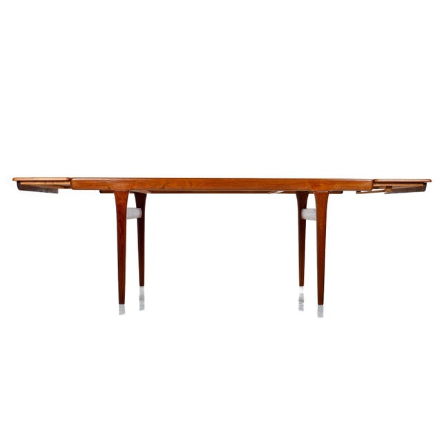 This large dining table stands firm in its solid pine core covered with a teak veneer. This hefty beauty boasts solid teak...