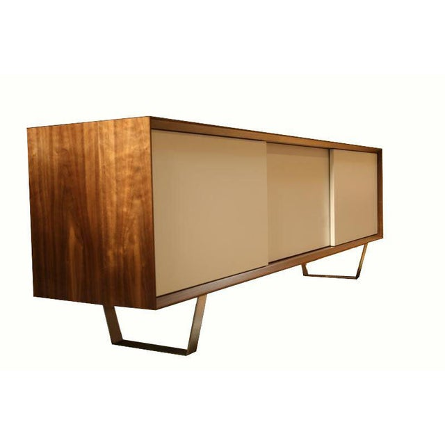 Mn Originals three-door Walnut credenza on polished stainless steel base. Active grain walnut Veneer case contrasted with...