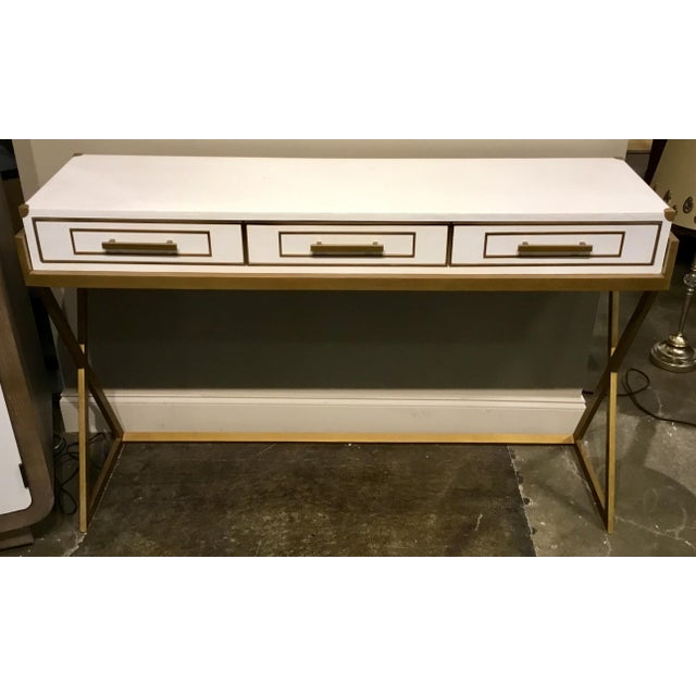 Stylish Currey & Co. modern regency white and brass console table, three drawers, textured white finish , showroom floor...