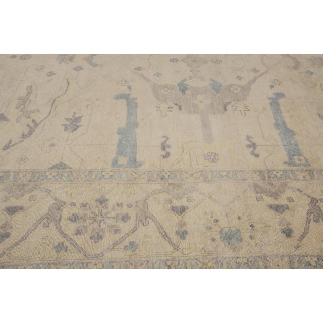 Hand-knotted rug with a floral design on a beige field with blue borders. This rug has magnificent detailing and would be...