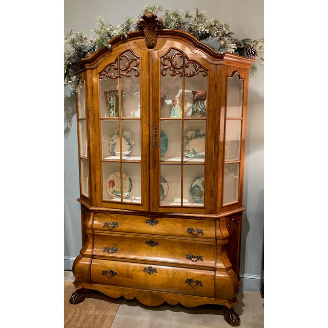 An early 20th century Dutch walnut bombe breakfront with double glass doors at top and three lower drawers all with...