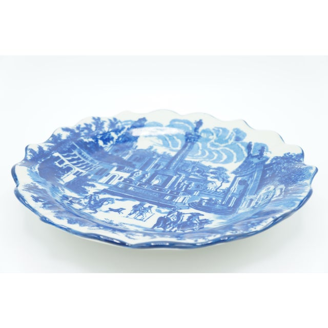 This is a 10 inch ironstone plate features a traditional blue and white town scene. With unique scalloped edges, this...