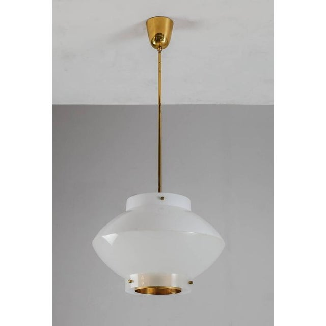 We have three oft hese white plexiglass model 61-380 pendant by Yki Nummi for Orno, Finland. The lamp has a brass ceiling...
