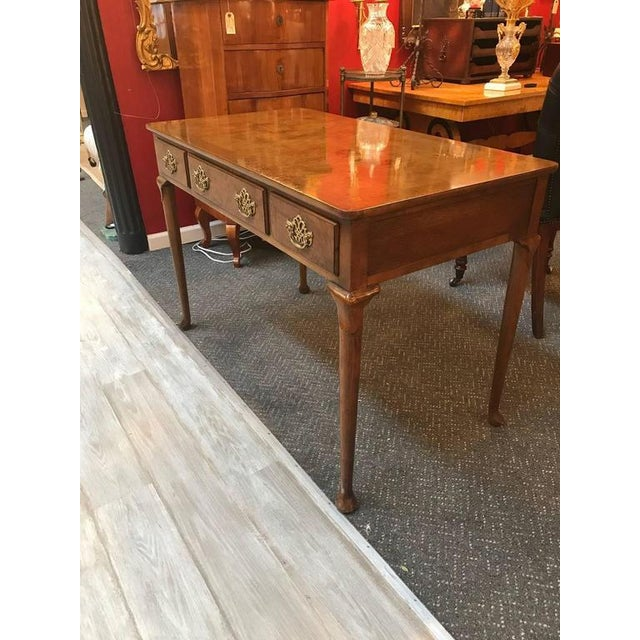 Classic English style writing desk by Baker. The burl walnut top is supported by four slightly carved Queen Anne legs with...