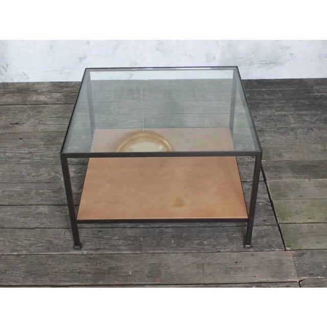 Square iron frame coffee table in bronze paint finish. Top shelf is clear glass and the bottom shelf is distressed leather...
