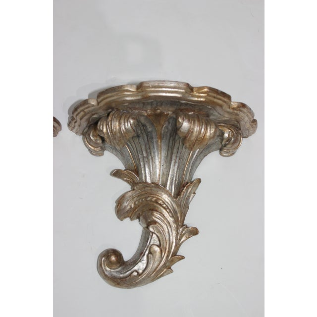 This stylish pair of Italian Louis XV style wall brackets are hand-carved wood with a silver leaf finish.