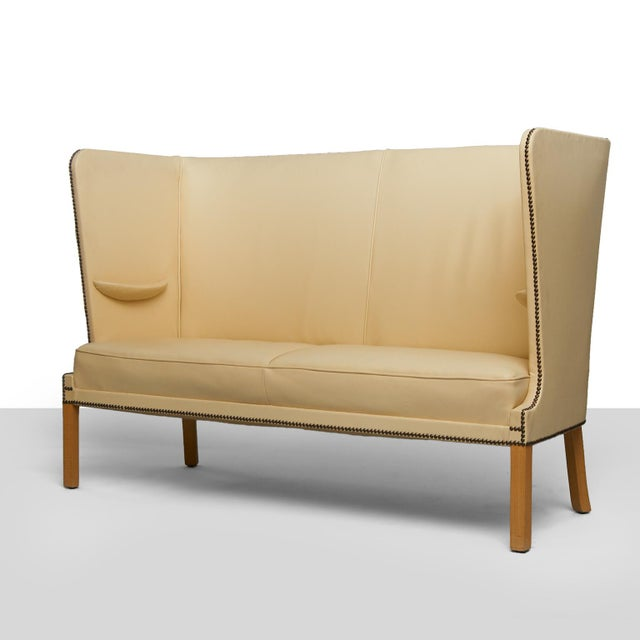 Frits Henningsen Settee A rare and nearly flawless Frits Henningsen settee of oak and its original ivory leather...