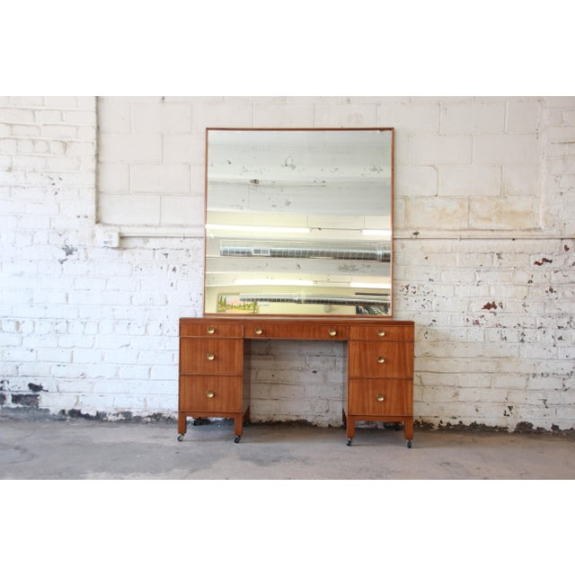 Offering a very rare and early vanity & mirror by Edward Wormley for Dunbar. The vanity offers seven drawers for ample...