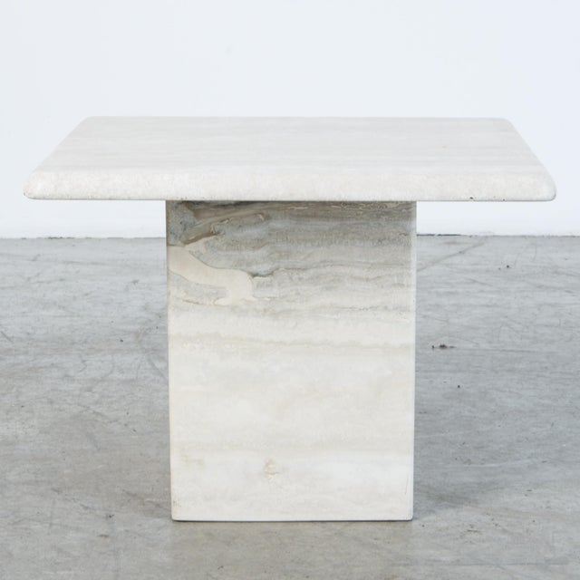 A refined travertine coffee table or pedestal, with rounded square top and base. A material rich in itself, echoing...