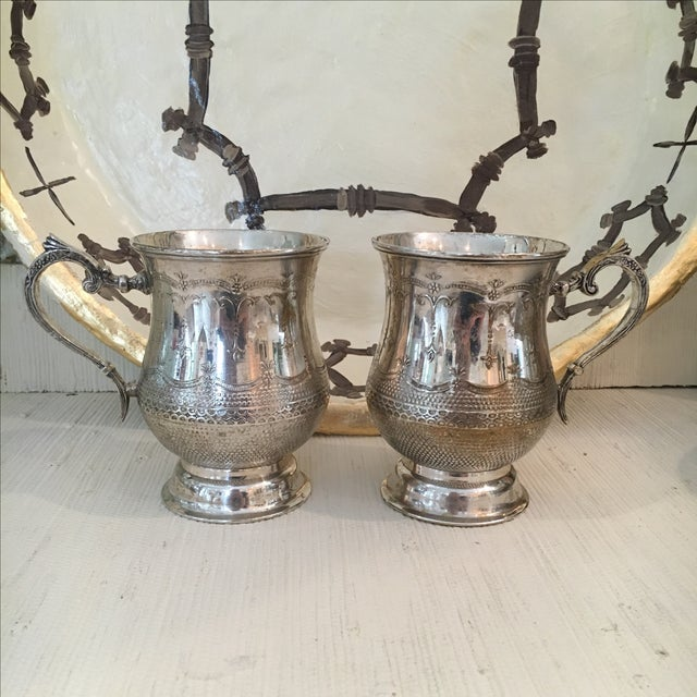 Offered is a pretty pair delicately etched silver plated mugs. These beauties are sure to make a statement in your elegant...