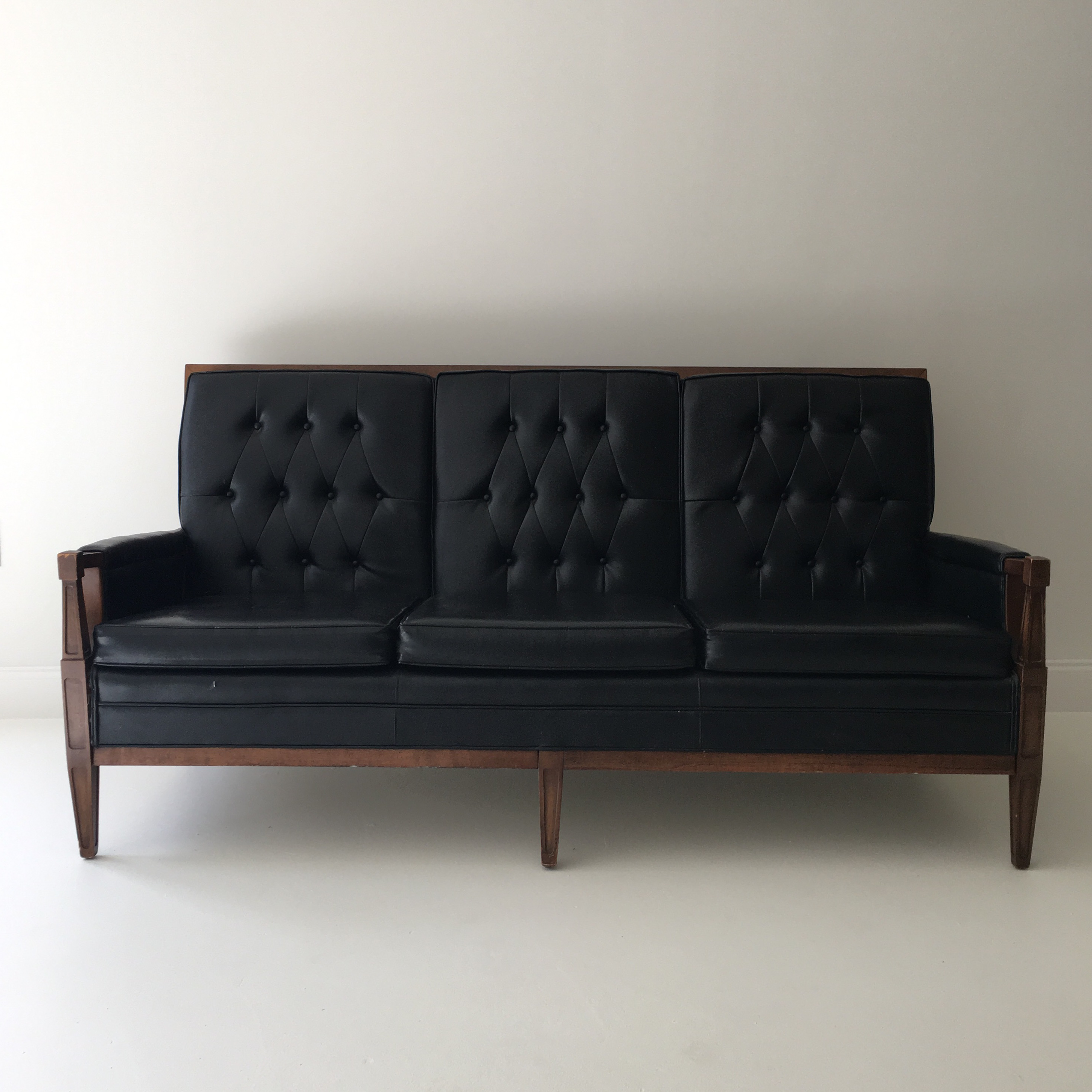 A Very Chic Black Leather Like Vinyl Sofa With A Wood Frame And Tufted Backs