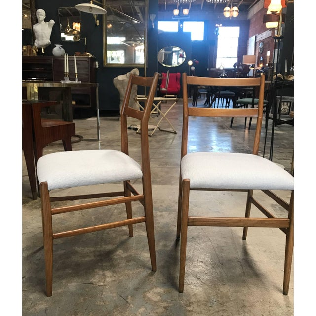 Pair of iconic Gio Ponti Superleggera dining chairs with upholstered fabric.