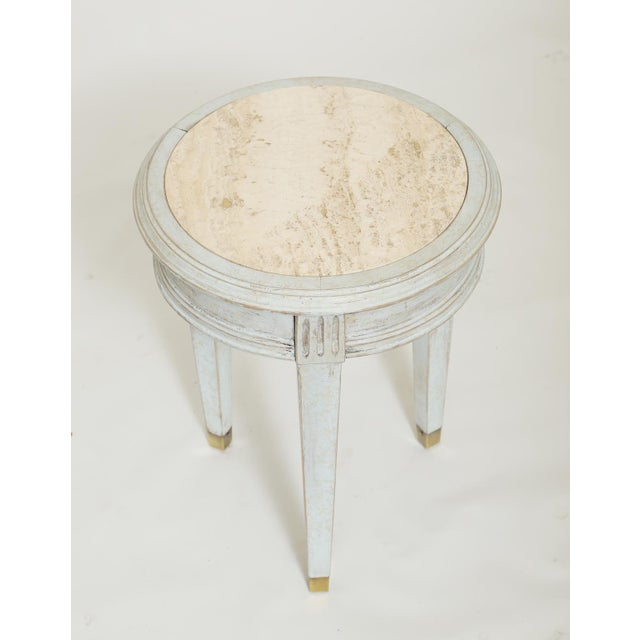 Accent table, having a light blue painted finish, showing natural wear, the travertine top inset into molded frame, on...