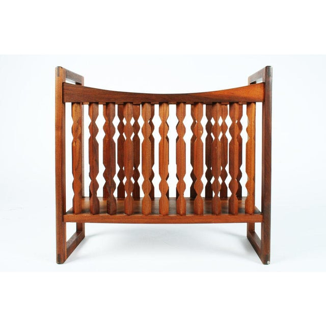 A wooden magazine stand in a crib-like form with an open frame of geometric spindles and rectangular ends that act as...
