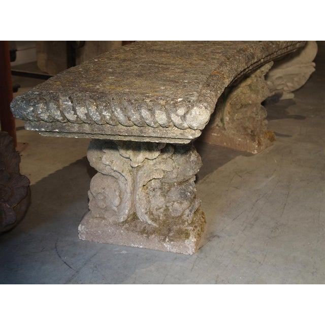 From France, this curved reconstituted stone bench has dolphin form motifs on the front and back of each leg. The tails of...