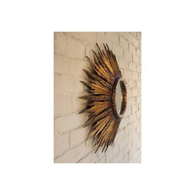 A midcentury French sunburst mirror, circa 1930 with feathered rays. Original mirror plate. The mirror is 6.5 inches in...