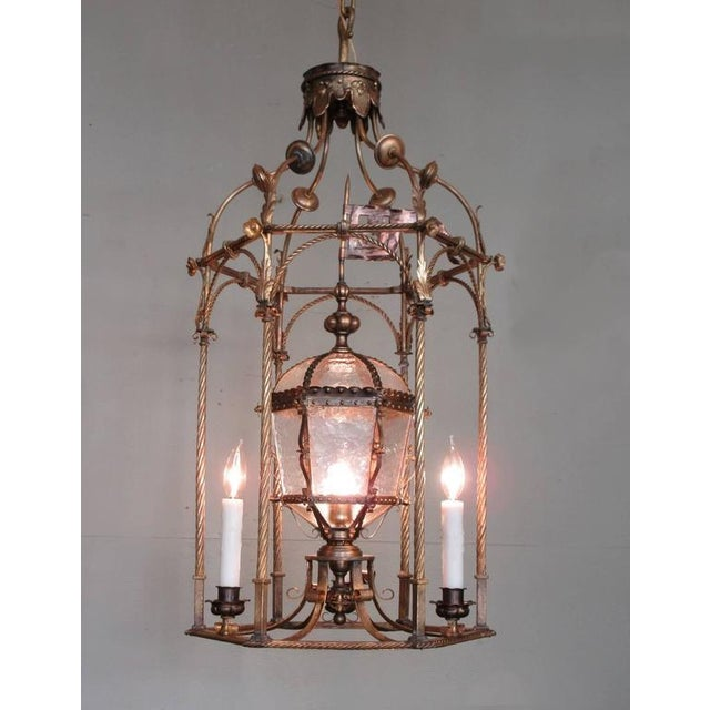 A grand Venetian gilt tole lantern, circa 1840, featuring three candles and original centre oil lamp accented with tole...